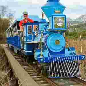 man in red shirt driving blue train